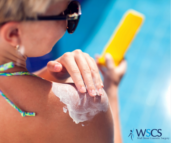 A woman at the pool putting sunscreen on her shoulder.